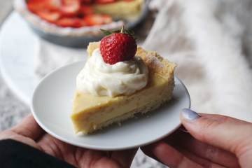 Homemade gluten free cream pie topped with cream cheese frosting and strawberries