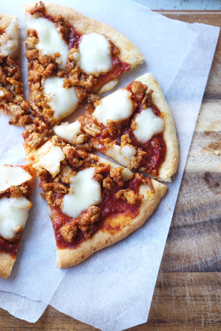 Gluten free pan de bono pizza base topped with pizza sauce, mozzarella and spicy pork