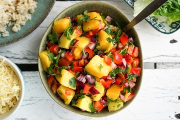 Delicious, healthy colourful mango salad with bell peppers, red onion, parsley, chilli and lime