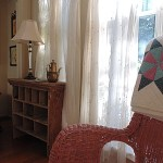 Wicker rocking chair and quilt in main bedroom.