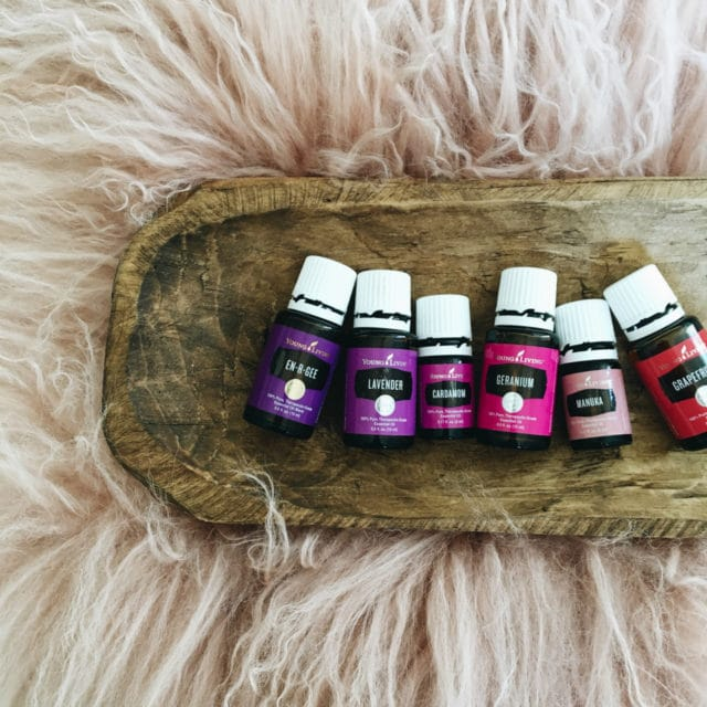 Essential oils from Young Living in a wooden bowl on a furry rug