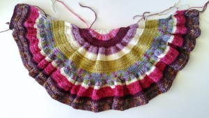 Crocheted crescent-shaped shawl made with scrap yarn.
