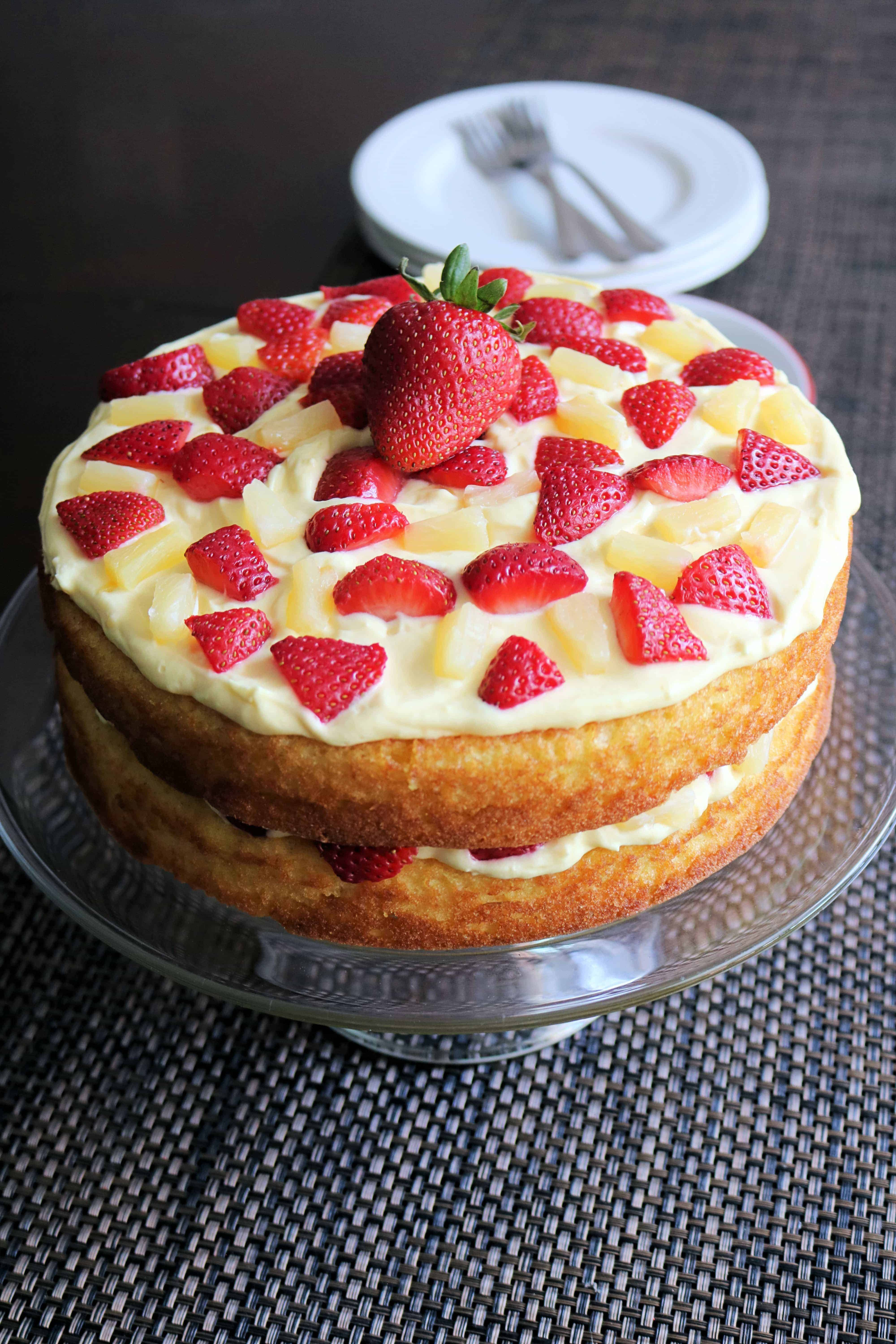 Craving a sweet dessert for your next potluck? Give this Luscious Strawberry Pineapple Cake a try! Made with a yellow cake mix, vanilla pudding, light whipped topping, and fresh strawberries and pineapples, this pineapple cake is the perfect, easy summer-time treat with a tropical twist! #cake #strawberry #pineapple #sweets #dessert