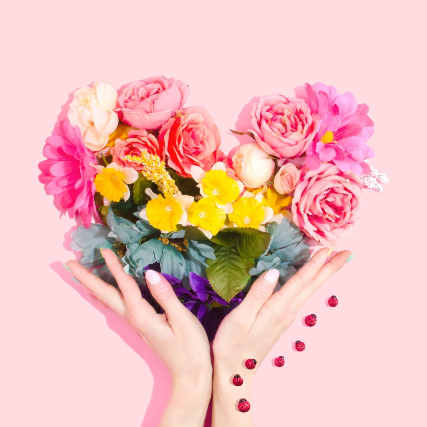 Hands holding an assortment of love shaped flowers