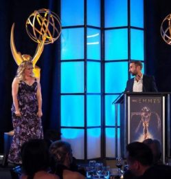 Kelvin Lawson – Director of Lisden Technology – on the podium at the Emmy Awards with host Kirsten Vangsness