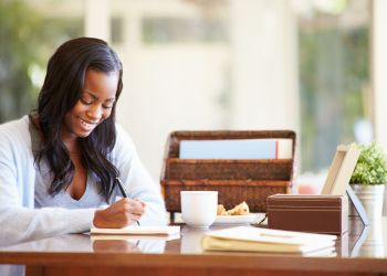 Woman Writing In Notebook Sitting At Desk