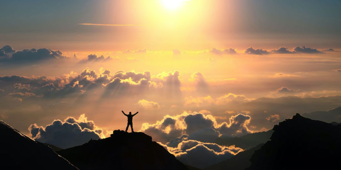 A man standing on the top of the mountain above the clouds. From 123rf