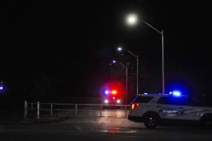 Kingston Police and Correctional Service Of Canada vehicles guard the perimeter around Collins Bay Penitentiary on Monday night.
