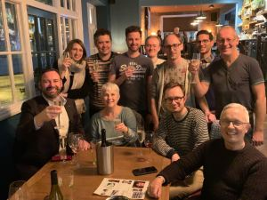 This is a photograph of some people at a previous pub quiz held at the Grove Pub in Surbiton. There are 11 people smiling and looking to the camera. Some of the people are holding drinks.