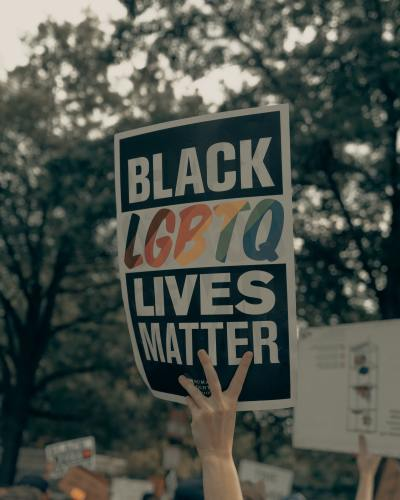 This image depicts a hand holding a sign that says, 'BLACK LGBTQ LIVES MATTER'