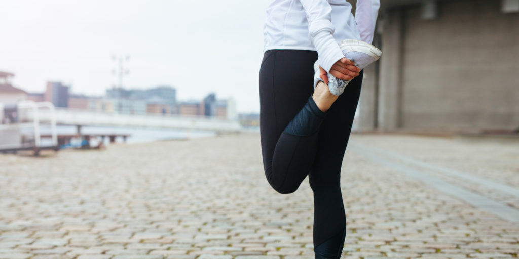 Fit young woman stretching her leg before a run