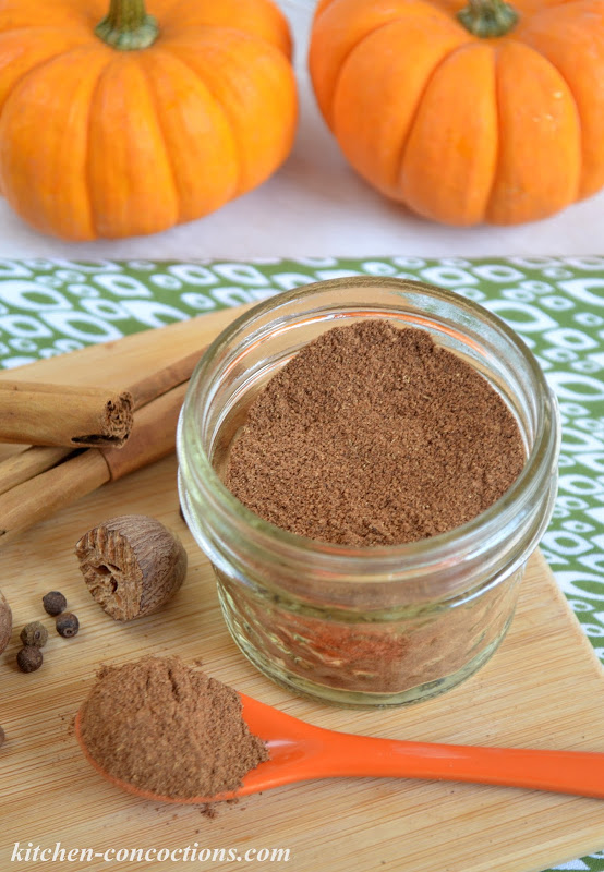 homemade pumpkin pie spice in a small mason jar on a wooden cutting board with some spice in an orange spoon with whole spices and small pumpkins in the background.
