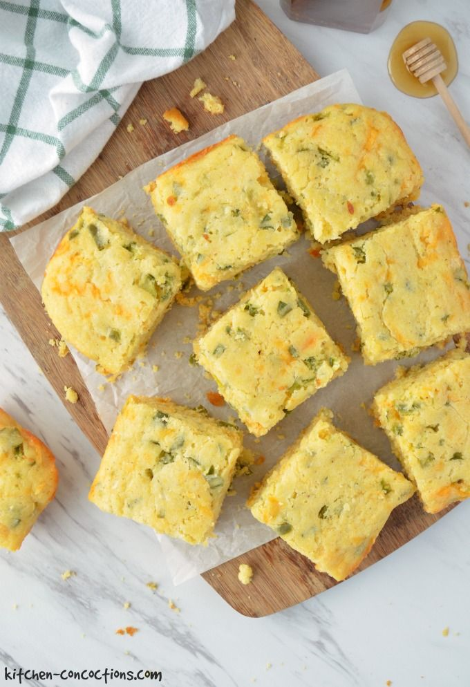Jalapeno Cheddar Cornbread Recipe - cornbread cut into squares on a cutting board with a honey stick on the side
