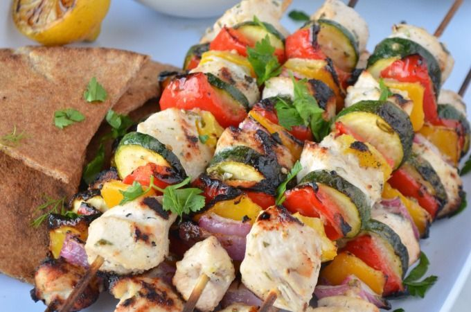 Greek Chicken Kebabs on a white serving platter with a side of grilled pita bread, grilled lemon wedges and a bowl of Homemade Tzatziki Sauce. A green and white striped towel is next to the platter.
