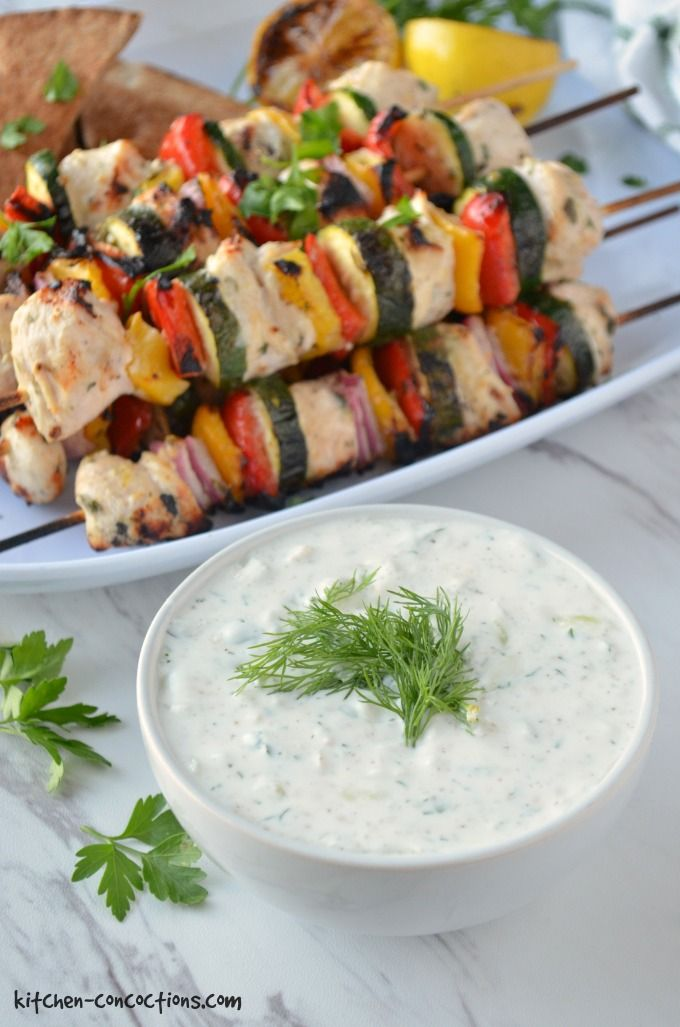 A white bowl filled with Homemade Tzatziki Sauce which is topped with fresh dill. The bowl is in front of a white platter that is topped with Greek Chicken Kebabs on a marbled counter top.