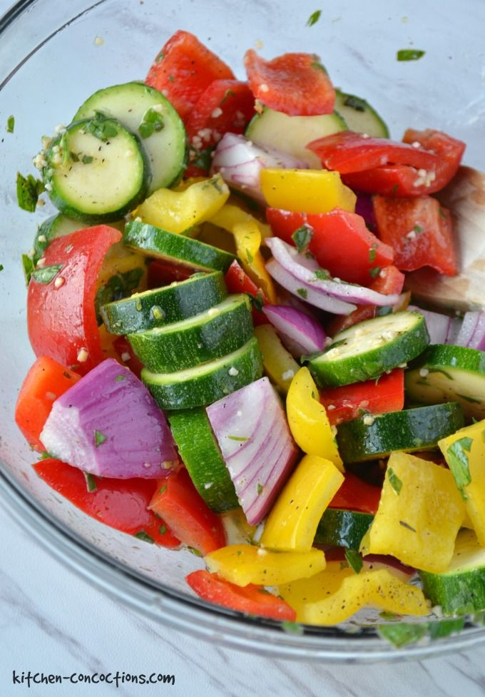 A close up photo of a bowl of diced yellow and red bell peppers, zucchini and red onions for Greek Chicken Kebabs.