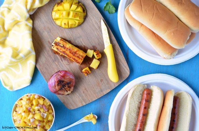 Hawaiian Hot Dogs image with grilled onions, pineapple and mango on a cutting board, a mango and pineapple relish in a small white bowl, grilled hot dogs in hot dog buns on a white paper plate