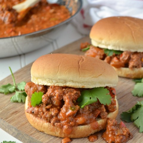 Bombay Sloppy Joes served on a potato hamburger bun and topped with a few pieces of fresh cilantro. Sloppy joes are placed on a wooden cutting board on a white wooden table. A skillet with the sloppy joe mixture and a white towel with a red stripe are in the background.
