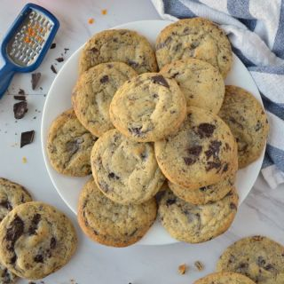 A plate of Orange Dark Chocolate Chunk Cookies with a white and blue striped towel on the right side and a small blue grater and orange on the left side.