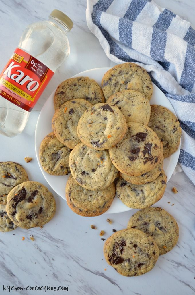 A plate of Orange Dark Chocolate Chunk Cookies with a bottle of Karo Corn Syrup lying next to the plate and a blue and white striped towel lying on the other side.