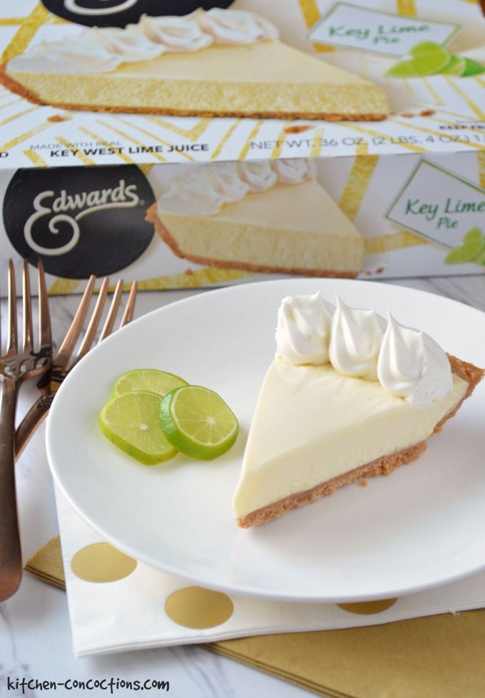 A slice of key lime pie on a white plate with three key limes on the side. The plate is set on top of a gold and white polka dot napkin and a solid gold napkin. Gold forks are on the side and a box of Edwards key lime pie is in the back ground.