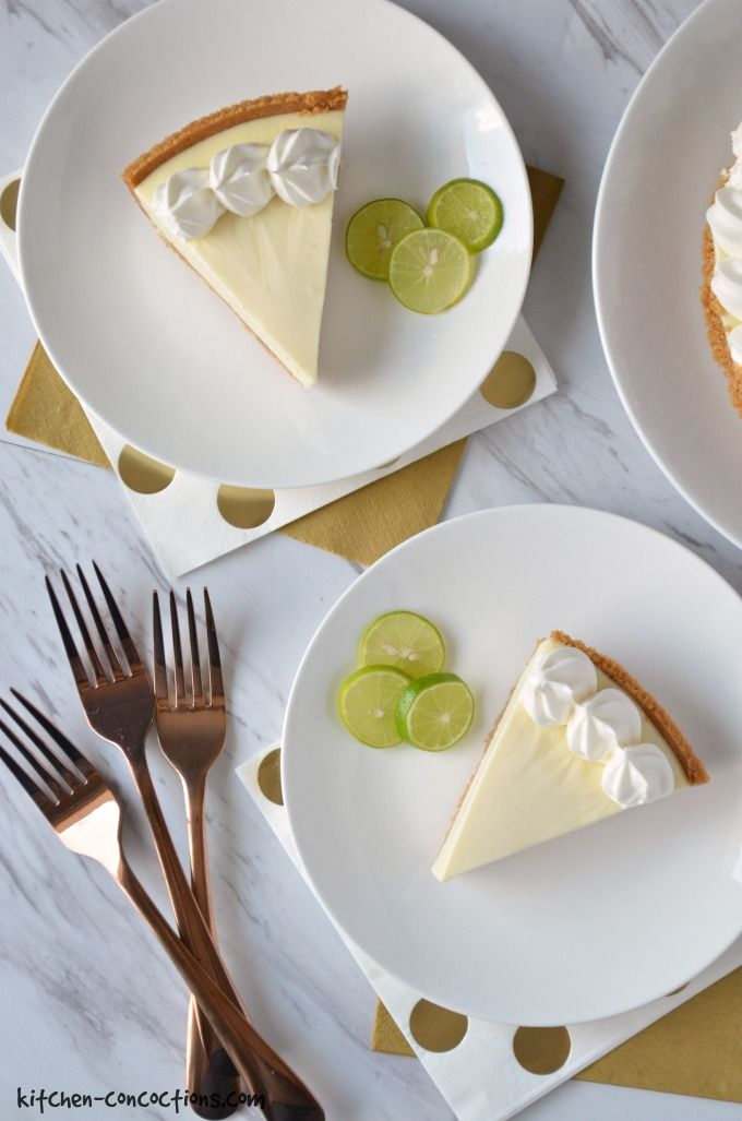 Two slices of key lime pie served on a white plates with three key limes on the side. The plates are set on top of a gold and white polka dot napkins and a solid gold napkins. Three gold forks are on the side.
