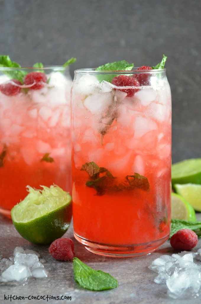 Two cocktail glasses filled with ice, raspberry syrup, mint and lime wedges to make a Raspberry Mojito. Ice, fresh lime wedge, fresh raspberries and fresh mint are on the table next to the glasses.