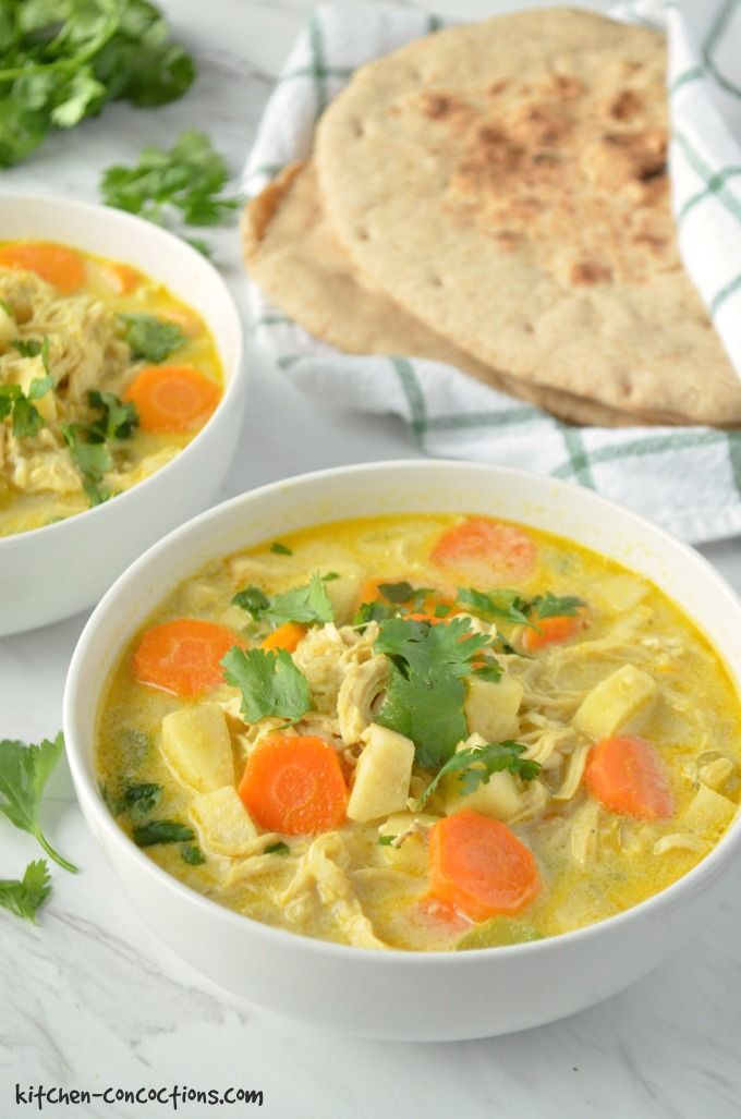 Chicken Mulligatawny Soup in a white bowl with silver soup spoons and naan wrapped in a green and white striped towel in the background.