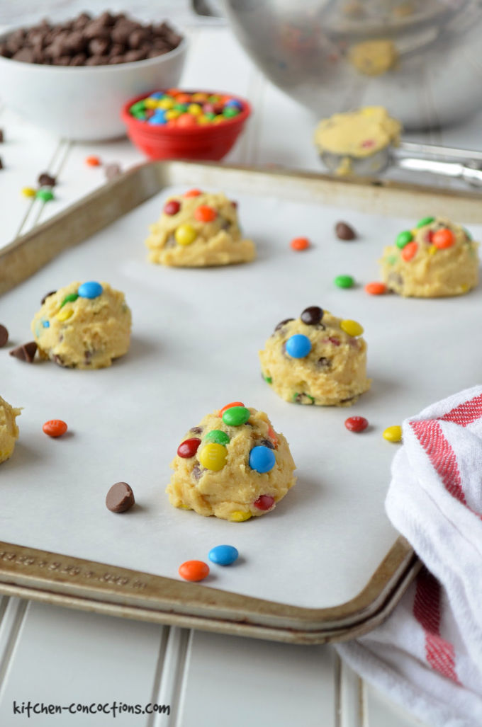 M&M's Cookie dough scooped onto a cookie sheet lined with a white parchment paper with small white bowl of chocolate chips and a small red bowl of M&M's in the background