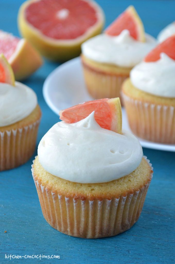 grapefruit cupcakes with cream cheese frosting a little slice of grapefruit on a piece of teal wood