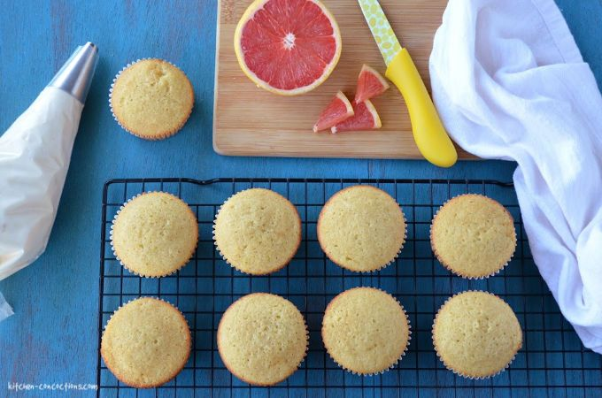 un-frosted pink grapefruit cupcakes sitting on a wire rack on top of a teal wooden board with a piping bag filled with cream cheese frosting and a wooden cutting board and sliced grapefruit on the side