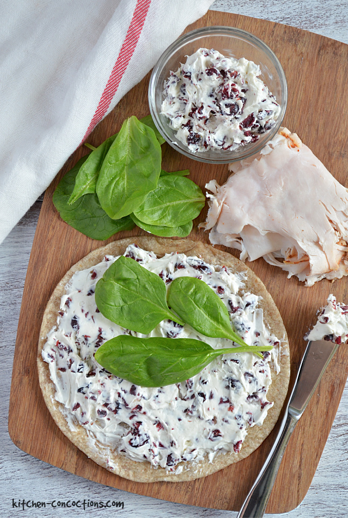 Turkey Cranberry Wrap being assembled on a wooden cutting board.