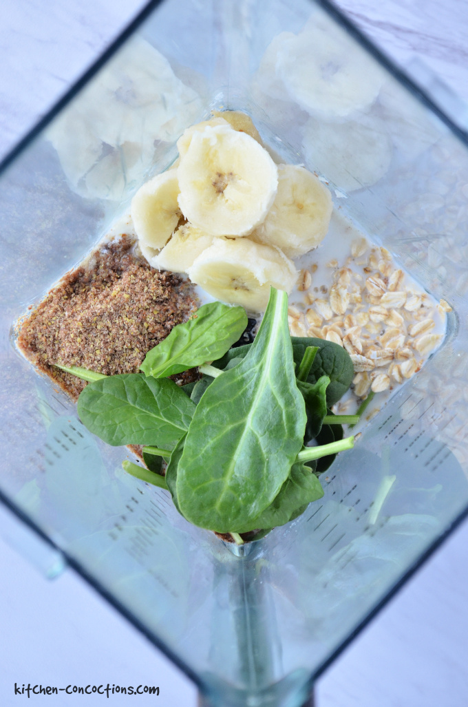 ingredients for spinach pancakes in a blender - showing fresh spinach, bananas, rolled oats, flax seeds