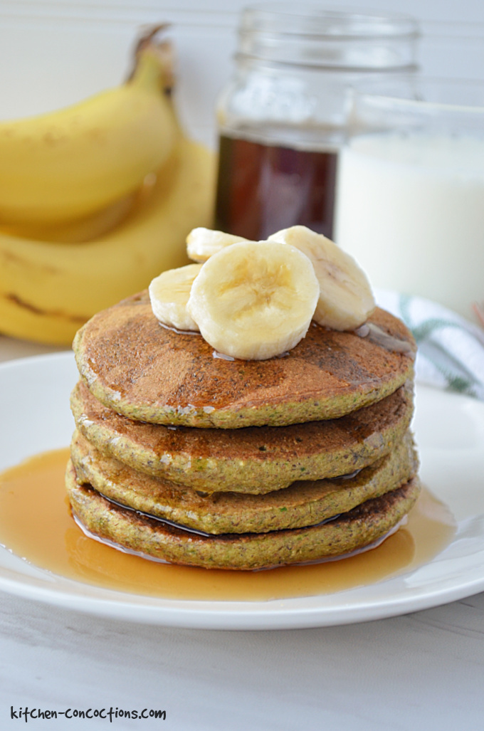 a stack of spinach pancakes on a white plate topped with sliced bananas and maple syrup and a bunch of bananas, jar of maple syrup and glass of milk in the background