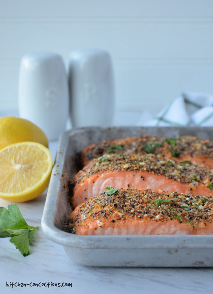 silver baking dish with three pieces of baked lemon pepper salmon parsley with a white salt and pepper shaker, green and white towel and whole lemon in the background