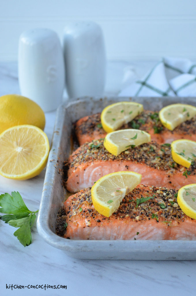 silver baking dish with three pieces of baked lemon pepper salmon topped with fresh lemon slices and parsley with a white salt and pepper shaker, green and white towel and whole lemon in the background