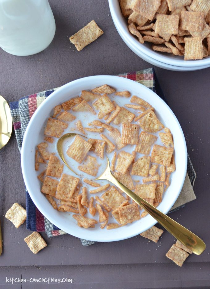 white bowl filled with cinnamon toast crunch cereal, milk and a gold spoon sitting on top of a dark brown wooden board