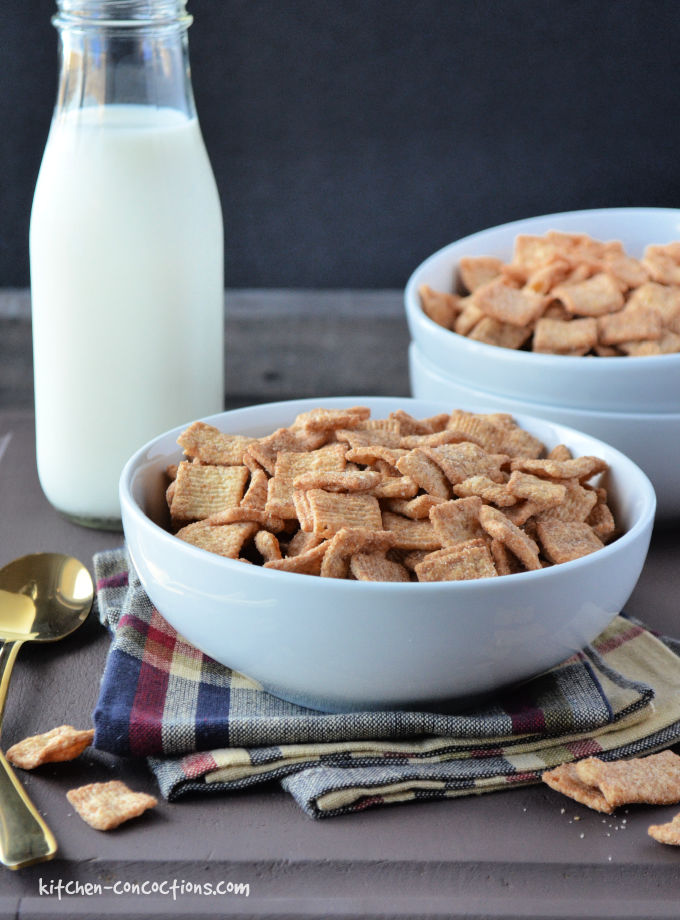 white bowl filled with cinnamon toast crunch cereal and a gold spoon sitting on top of a dark brown wooden board and tan, blue and red striped towel with a jar of milk in the background