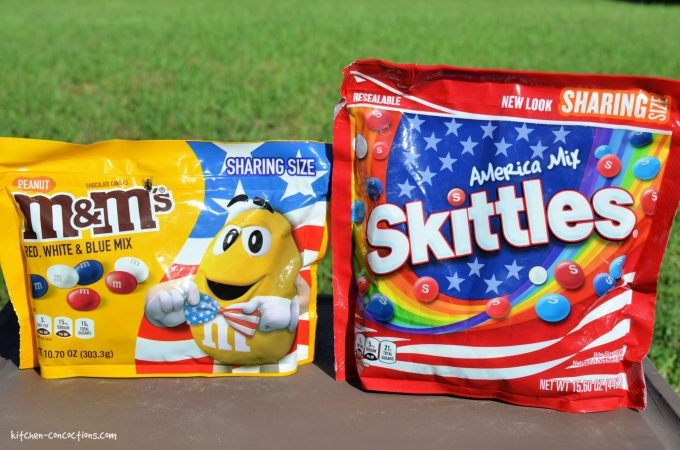 A bag of red, white and blue M&M's and a bag of red, white and blue Skittles sitting on a wooden table outside.