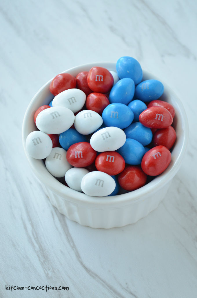 A white bowl filled with red, white and blue peanut M&M's sitting on a marble counter.