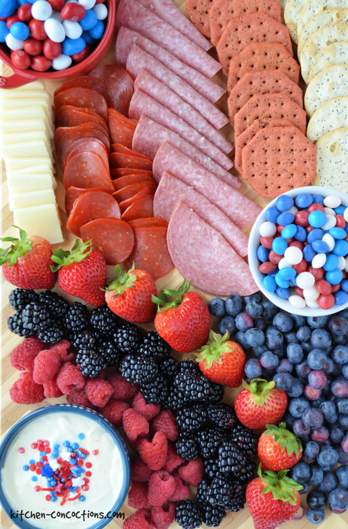 close up photo of a 4th of July Charcuterie Board featuring a red bowl filled with red, white and blue m&m's, a white bowl filled with red, white and blue Skittles, a blue bowl filled with fruit dip and assorted fruit, meats, cheeses and crackers