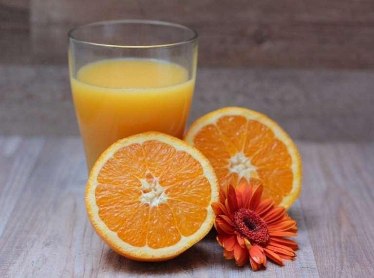 Ein Glas Orangensaft mit zwei Orangenhälften und einer Blume davor auf einer Holzoberfläche