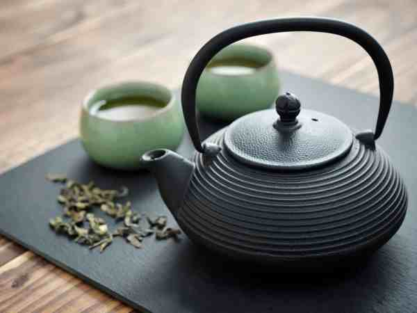 54947511 – green tea in cast-iron teapot with  small cups over wooden background