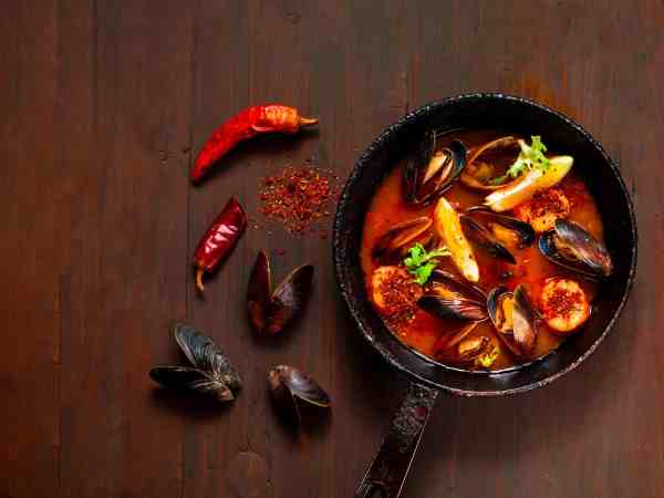 Mussels in red curry sauce on a wooden background.The concept of  healthy and satisfying appetizer or light meal.