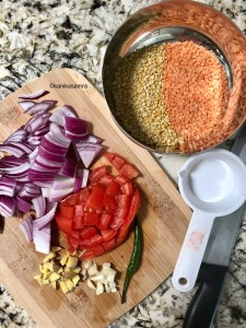 A chopping baked with chopped onion, tomato, whole green chilli, chopped ginger and garlic and a bowl of soaking moong and masoor dal.