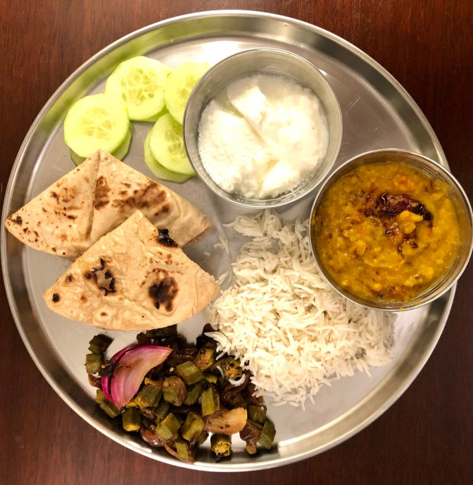 Indian meal on a steel plate with dal, dahi, rice, roti and sabzi