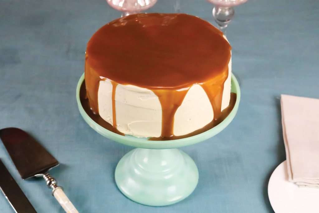 A super moist gingerbread layer cake with caramel buttercream and a rich caramel sauce cascading down the top and hidden inside. Hello christmas in a cake!