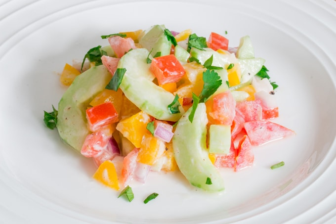 An Indian inspired cucumber salad with tomatoes, peppers, and red onion with a yogurt and lemon dressing that's delicious on it's own, or as a way to cool the spice from another dish.