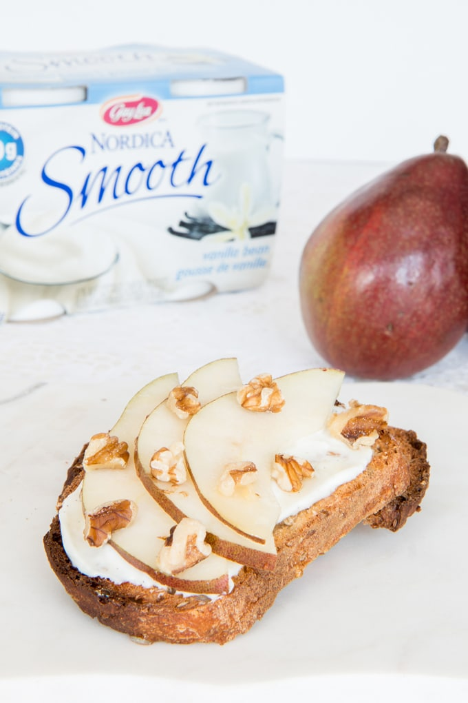 Cheese and pears on a crispy slice of whole grain bread drizzled with honey and topped with walnuts. A low fat, high protein snack that satisfies!