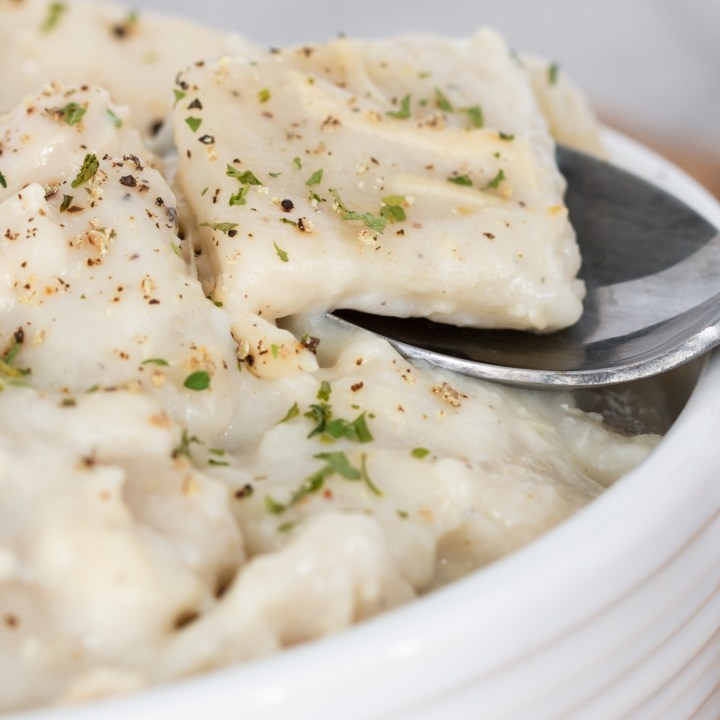 A copycat version of cracker barrel chicken and dumplings sitting in a white ceramic bowl